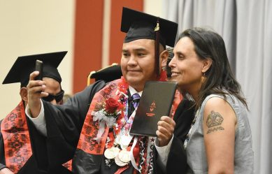 Navajo Times | Donovan Quintero Cyrus Coan from West Valley City, Utah, takes a selfie with Navajo Technical University guest speaker Winona LaDuke on Friday during commencement in Crownpoint.