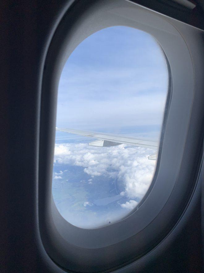 Hublot d'un avion, avec vue sur le ciel, pour parler de ce qu'il faut mettre dans sa valise pour un week-end.