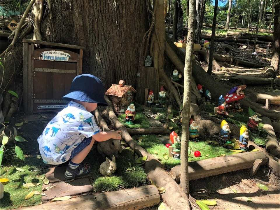 """Kumbartcho Sanctuary Fairy Garden - little boy crounched in front of a door that says """"this is the home of Peter Rabbit""""."""