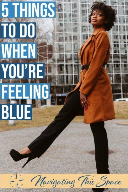 Model wears a rust brown long coat, raises one leg while wearing long heel boats
