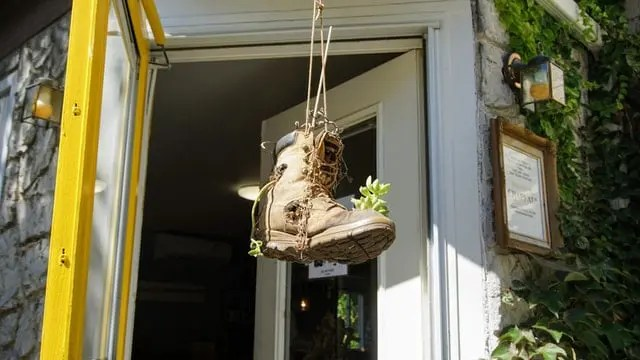 An old boot repurposed as a plant pot hanging outside the front door of a house