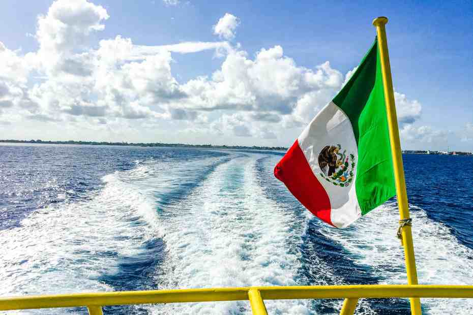 Mexican flag on the back of a ferry overlooking a favorite Mexico Vacation Spot, the island of Cozumel