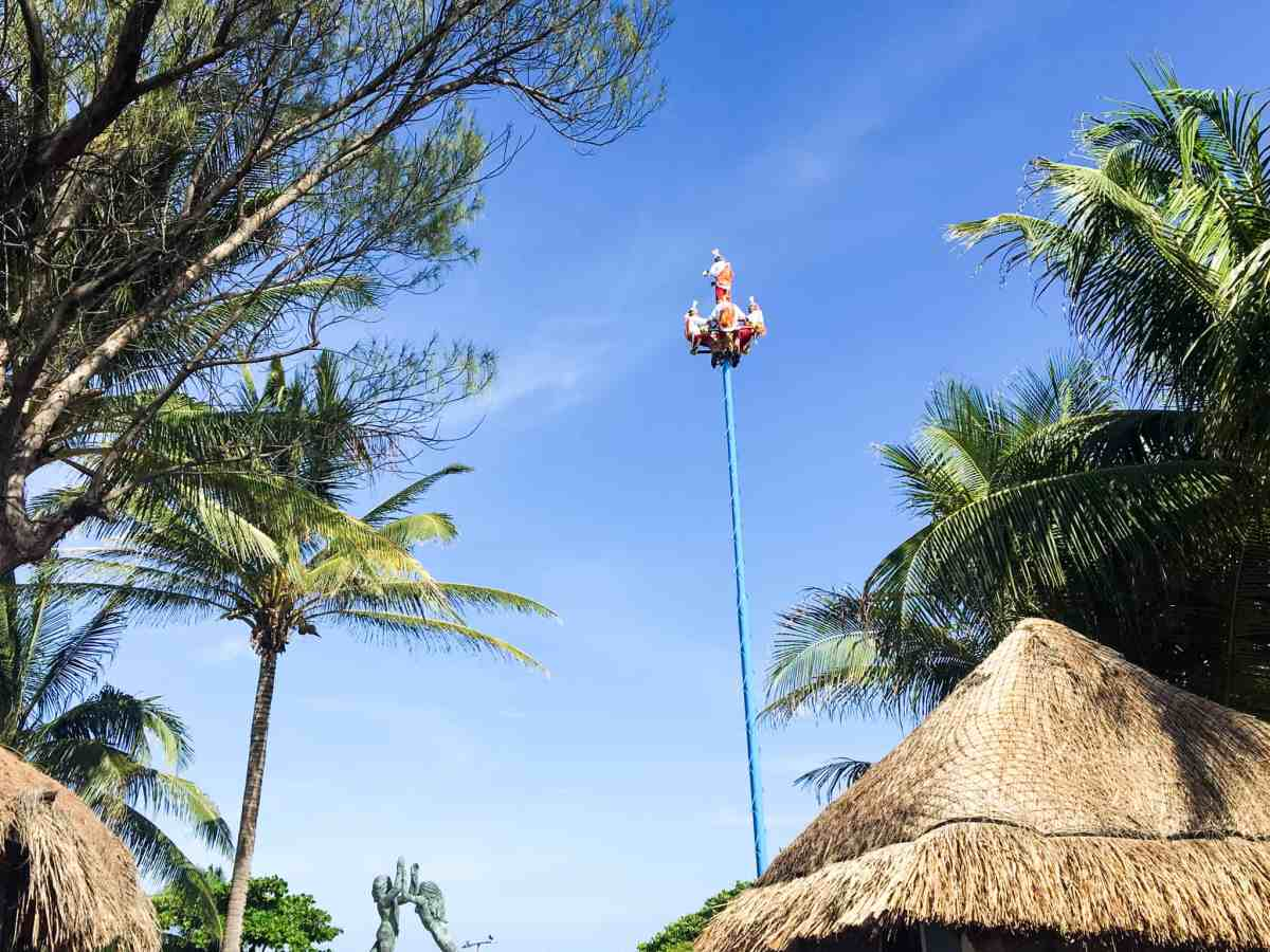 sky performers on a high pole performing in Playa Del Carmen's pier