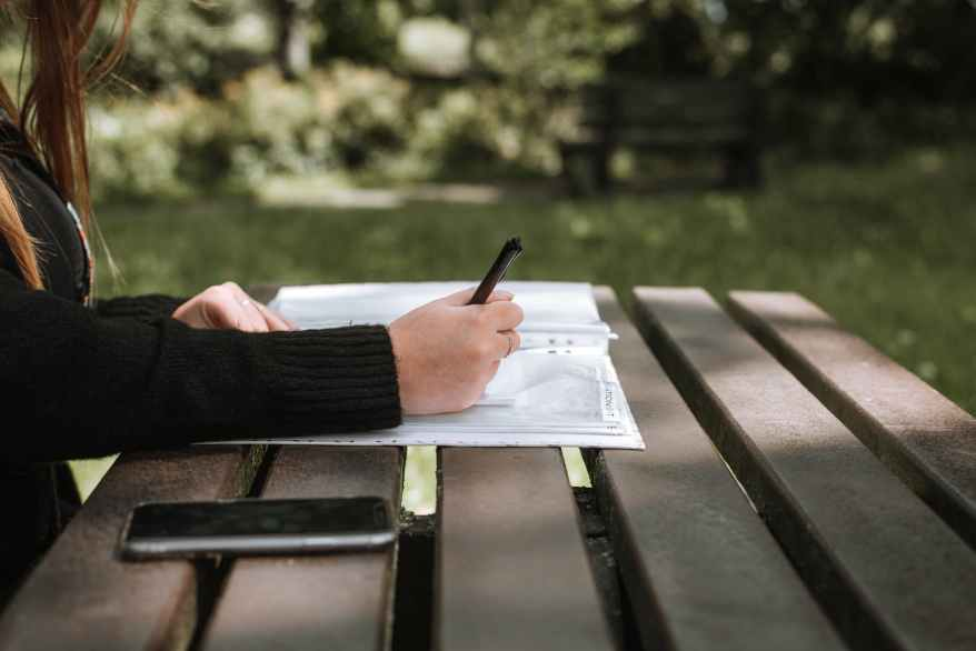 faceless woman taking notes in copybook in park, road tripping during the pandemic