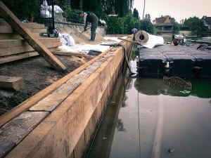Как выполнить укрепление берега деревом на участке возле водоема?