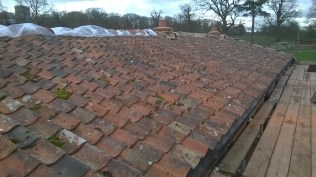 Roof nearly done...lovely re use of old tiles