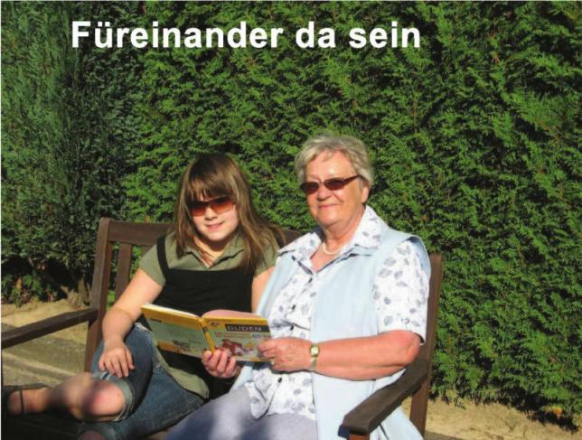 Im Vordergrund einer Zypressenhecke sitzt eine Oma mit Ihrer Enkeltochter auf einer Holzbank und schauen sich ein Buch an.