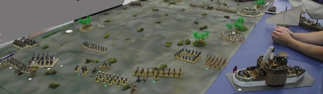 Sudanese infantry advances along the river supported by the gunboat.