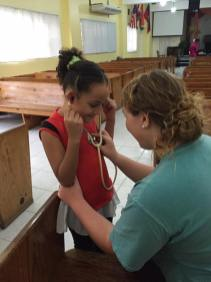 Sarah Lenahan, a Butler pharmacy student, allows a young girl to try out a stethoscope.
