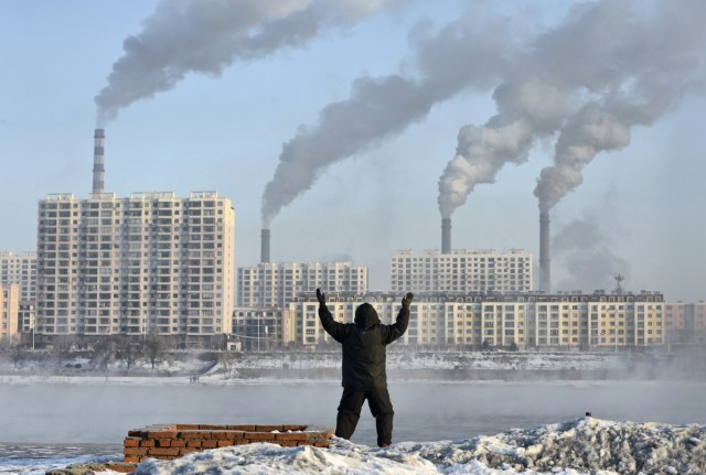 An elderly man exercises in the morning as he faces chimneys emitting smoke behind buildings across the Songhua river in Jilin