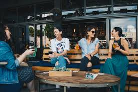 A group of people sit around a table talking and drinking coffee.