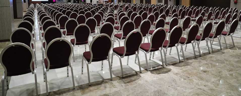 A large empty hall with all the chairs set out for a convention