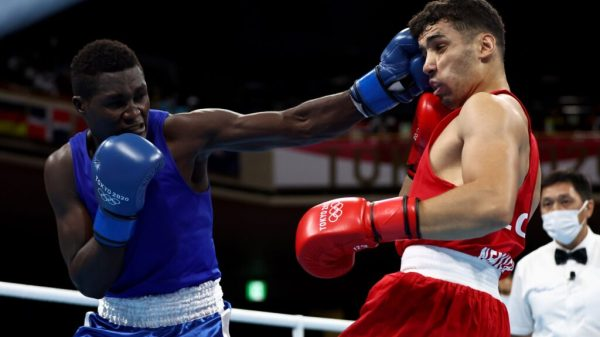 PHOTO COURTESY: Ugandan Boxer David Kavuma Semujju (Blue) takes on Algerian Younes Nemouchi (Red) in Round 2 at the last 32 Kokugikan Arena