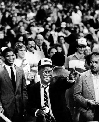 "Chicago's first Black Mayor, Harold Washington prepares to throw out the first ball before the start of a Sox game. One of his staff asst. Bill,""Doc,"" Walls is seen just behind his left shoulder and his Corporation Councel Attorney James Montgomery on the right. Photo by Bob Black"