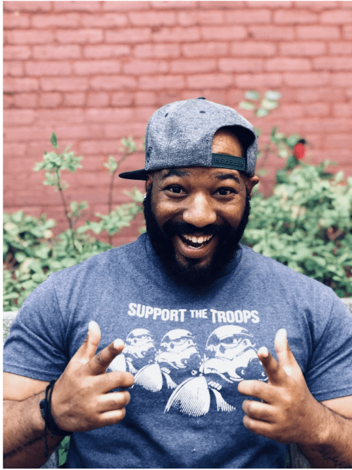 AJ, a Black man with a dark beard, is wearing a grey cap sideways and a grey Star Wars shirt. He is giving two thumbs up and smiling at the camera.