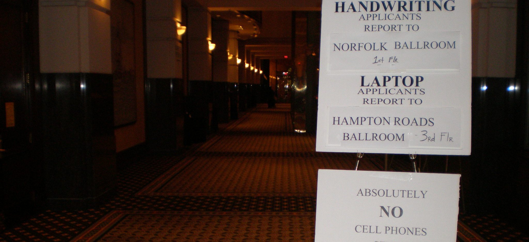 A sign telling handwriting applicants for the bar to go to the Norfolk Ballroom and more instructions for the bar exam are in the foreground. The background is a stately hotel where one of the Virginia Bar Exams took place in 2008.