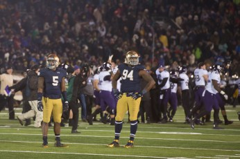 Irish freshman linebacker Nyles Morgan, left, and junior defensive lineman Jarron Jones stand on the field while Northwestern celebrates its 43-40 overtime victory over Notre Dame on Saturday at Notre Dame Stadium.