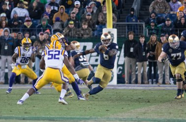 Irish quarterback Malik Zaire runs around defenders.
