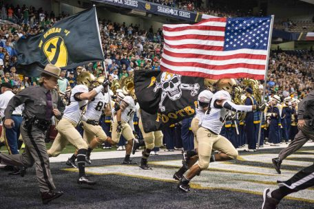 Army players run onto the field at the Alamodome carrying the American flag.