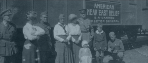 Relief workers, soldiers and children standing close to Near East Relief sign on a train.