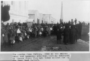 Armenian and Greek Families, men, women, and children leaving Turkey after the genocide. People are holding sacs and bags with their personal belongings. People are waiting for the aid of the Near East Relief.