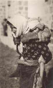A photo of a mother carrying her child on her back. Her hair is covered.
