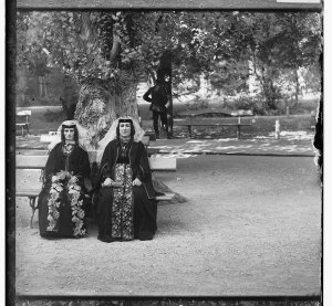 Two Armenian women wearing their folklore outfit, seating under a big tree.