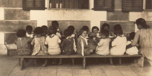 Children dining at a small table outdoors at the Birds' Nest Orphanage