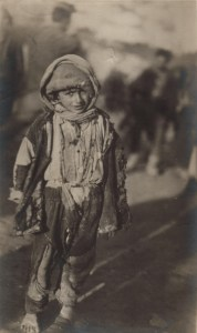 Refugee child  in rags. Children struggled to keep covered in the extreme climate. Many suffered from sunburn and frostbite. Nellie Miller's original caption reads: