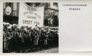 Postcard of Near East Relief orphans in Constantinople. A group of Near East Relief boys in Boy Scout uniforms greet the first large group of American tourists to visit Constantinople since World War I began. Despite the ongoing political situation, the Near East maintained a thriving tourism trade. Visitors from America purchased orphan-made souvenirs and postcards like this one to benefit Near East Relief's work.