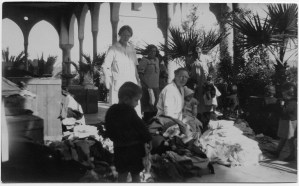 Based on Nellie Miller's notes, Maria Jacobsen (right) is unpacking supplies sent from Denmark. Miss Jacobsen ran the Birds' Nest on behalf of Near East Relief, but she was also a missionary with a Danish organization.