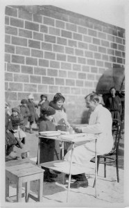 Dr. Russell Uhls ministers to patients in winter clothing in the orphanage courtard. Many of the first Near East Relief volunteers were physicians and nurses. Dr. Uhls was an ophthalmologist who specialized in the treatment and prevention of trachoma.
