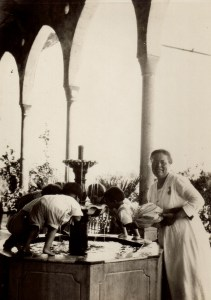 Danish missionary and Near East Relief worker Maria Jacobsen holds a child up for a drink of water from the fountain on the terrace at the Birds' Nest orphanage. Nellie Miller's original caption reads: