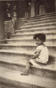 Child sitting on the steps at the Birds' Nest Orphanage. Nellie Miller Mann identifies this child as