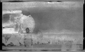Damaged photograph of a refugee woman standing in front of a city of tents