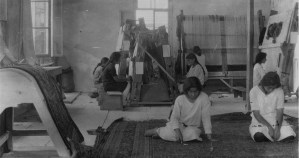 Young Armenian women weaving rugs in a small workplace with windows on the sides.