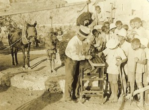 Relief worker and agricultural specialist Fred Midgley (in white hat) teaches farming skills to a group of Near East Relief orphans at the agricultural school at Syra. The children living at the Syra Orphanage were survivors of the genocides against the Ottoman Armenians and the Anatolian Greeks.
