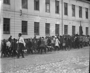 Large group of children walking past a white building with a Greek motif along the top. One of the boys carries a flag. The children are not dressed in matching uniforms. It is possible that they are students rather than orphans.
