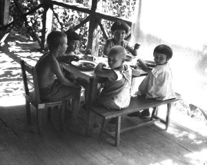 Children eating at a small table on a wooden porch.