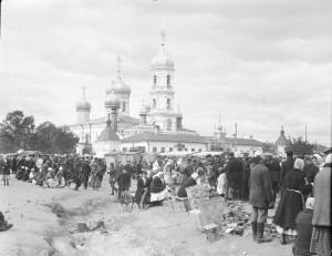 Marketplace with Orthodox church in background. It is unclear if the people in the photograph are refugees; they appear quite well-dressed.