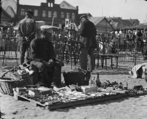 Man selling items from a wooden panel in an outdoor market. The objects in the middleground are chair and bedframes.