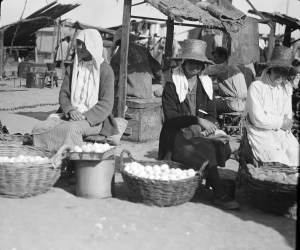 Women selling eggs from baskets in an outdoor marketplace.