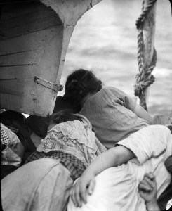 Woman and girls sleeping under a boat