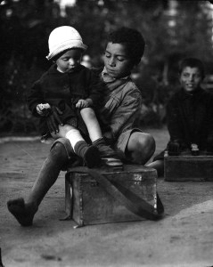 An older boy sits on a small trunk with a younger boy in his lap.