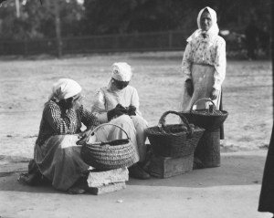 Three women with large baskets. The women wear aprons and traditional Russian-style head scarves.