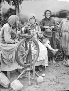 A group of women gathered around a spinning wheel. Two of the women are knitting. The ability to spin and knit helped women to be more self-sufficient.