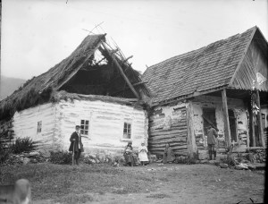 Three women sit in front of two dilapidated buildings. One woman holds a child. The woman in the center might be dressed as a nurse. There are two men standing on either side.
