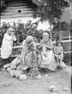 Two women sit at a spinning wheel. One woman knits. Two children look on.