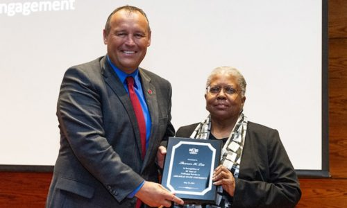 Sharon K. Lee receives plaque presented by Chancellor Kelly Damphousse
