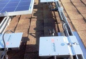 Micro inverters and solar panels mounted on a rail system on a residential shingle roof. The rail system keeps the panels cool and is attached to quick mount roof flashing that prevents the roof from leaking.